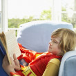 Boy sitting in armchair and reading — Stock Photo #33862243