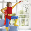 Boy standing on armchair and pointing — Stock Photo #33866227