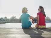 Women sitting on pier back view — Stock Photo