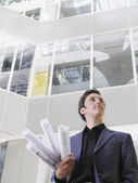 Business man holding rolled blueprints — Foto de Stock