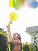 Girl with balloons smiling — Stock Photo