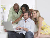 Adults on sofa looking at laptop — Stock Photo