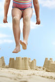 Girl  jumping on sand castle — Stock Photo