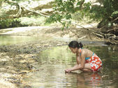 Woman squatting in lake — Stock Photo