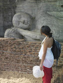 Woman looking at statue of Buddha — Stock Photo