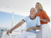 Couple at helm of yacht — Stock Photo
