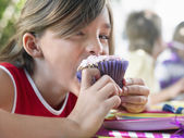 Girl eating cupcake — Stock Photo