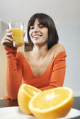 Woman holding glass with orange juice — Stock Photo