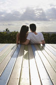 Teenage couple sitting on deck — Stock Photo