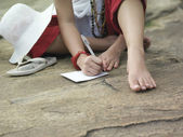 Woman sitting on rock writing — Stock Photo