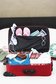 Open suitcase on bed — Stock Photo