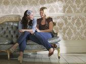 Amigos sentados juntos no sofá — Fotografia Stock