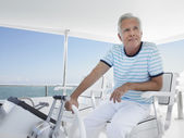Man sitting at helm of yacht — Stock Photo