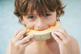 Boy eating slice of melon — Foto Stock