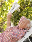 Man reclining on lounge chair — Stok fotoğraf