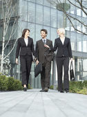 Three business people walking — Stock Photo