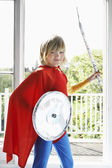 Boy holding toy shield and sword — Stock Photo