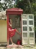 Woman using pay phone — Stock Photo