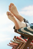 Person resting on deckchair on beach — Stock Photo