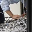 Man working on tangle of computer wires — Stock Photo #33870411