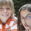Boy and Girl with Magnifying Glass — Stock Photo #33878771