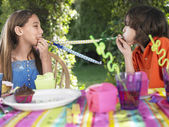 Girls blowing party puffers — Stock Photo