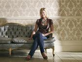 Woman Sitting on Ornate Sofa — Stock Photo