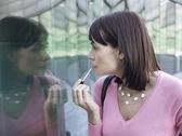 Woman applying lip gloss — Stock Photo