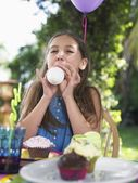 Girl blowing up balloon — Stock Photo