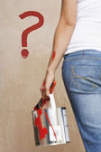 Woman holding painting can and question mark — Stock Photo