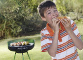 Boy eating frankfurter — Stock Photo