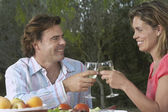 Couple toasting in garden — Stock Photo