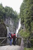 Man and woman watching waterfall — Stock Photo