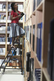 Office worker on ladder in file storage room — Stock Photo
