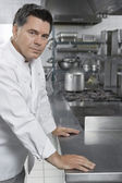 Male chef standing  in kitchen — Stock Photo