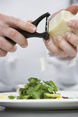 Male chef grating cheese over salad — Stock Photo