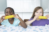 Two Girls Eating Corn — Stock Photo