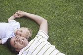 Baba ve genç oğlu çim üzerinde yalan — Stok fotoğraf