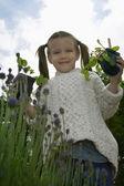Girl holding plants — Stock Photo