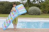 Boy  blowing up air mattress — Stock Photo