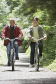 Man and middle-aged woman riding bicycles — Stock Photo