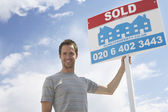 Man holding sold sign — Stock Photo