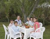 Family sitting garden table — Stock Photo