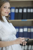 Office worker with palmtop in file storage room — Stock Photo