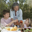 Woman serving fruit to children — Stock Photo #33881789