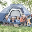 Family smiling from a tent — Stock Photo #33885063