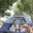 Family smiling from a tent — Stock Photo #33889053
