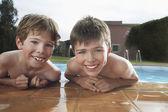 Boys leaning on edge of pool — ストック写真