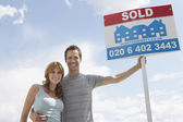 Couple holding Sold Sign — Stock Photo