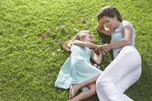 Mother and daughter lying on lawn — Stok fotoğraf